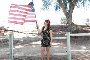 Woman Raising the US Flag | Veteran Car Donations